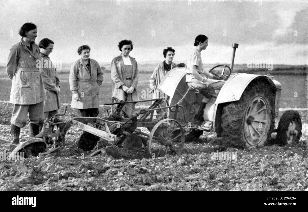 British girls of the Women's Land Army learning to plough with a tractor. World War II - Stock Image