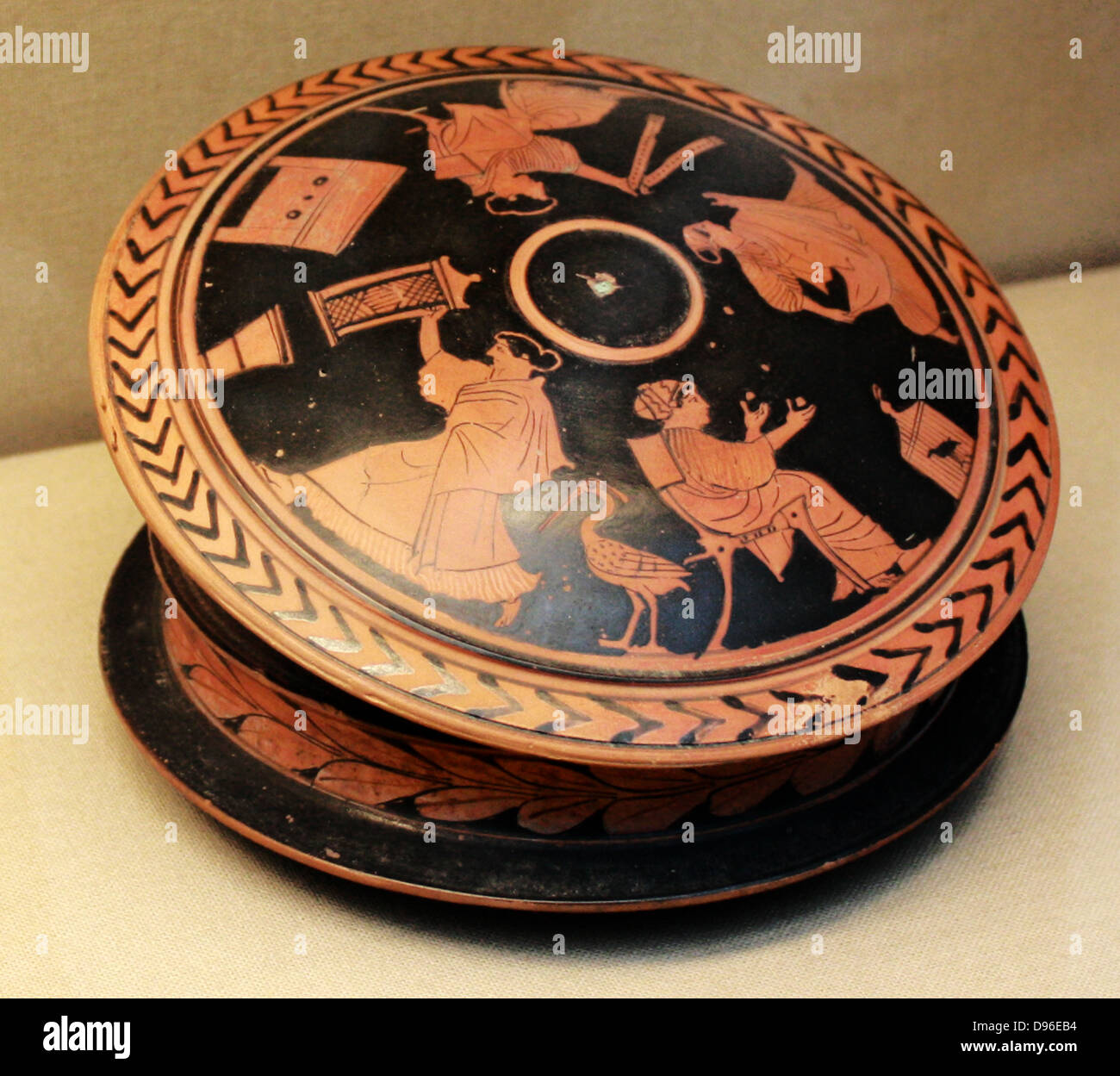 Red-figured pyxis (trinket-box) with a lid showing a woman holding a 'sprang' frame. Greek, ,made in Athens - Stock Image