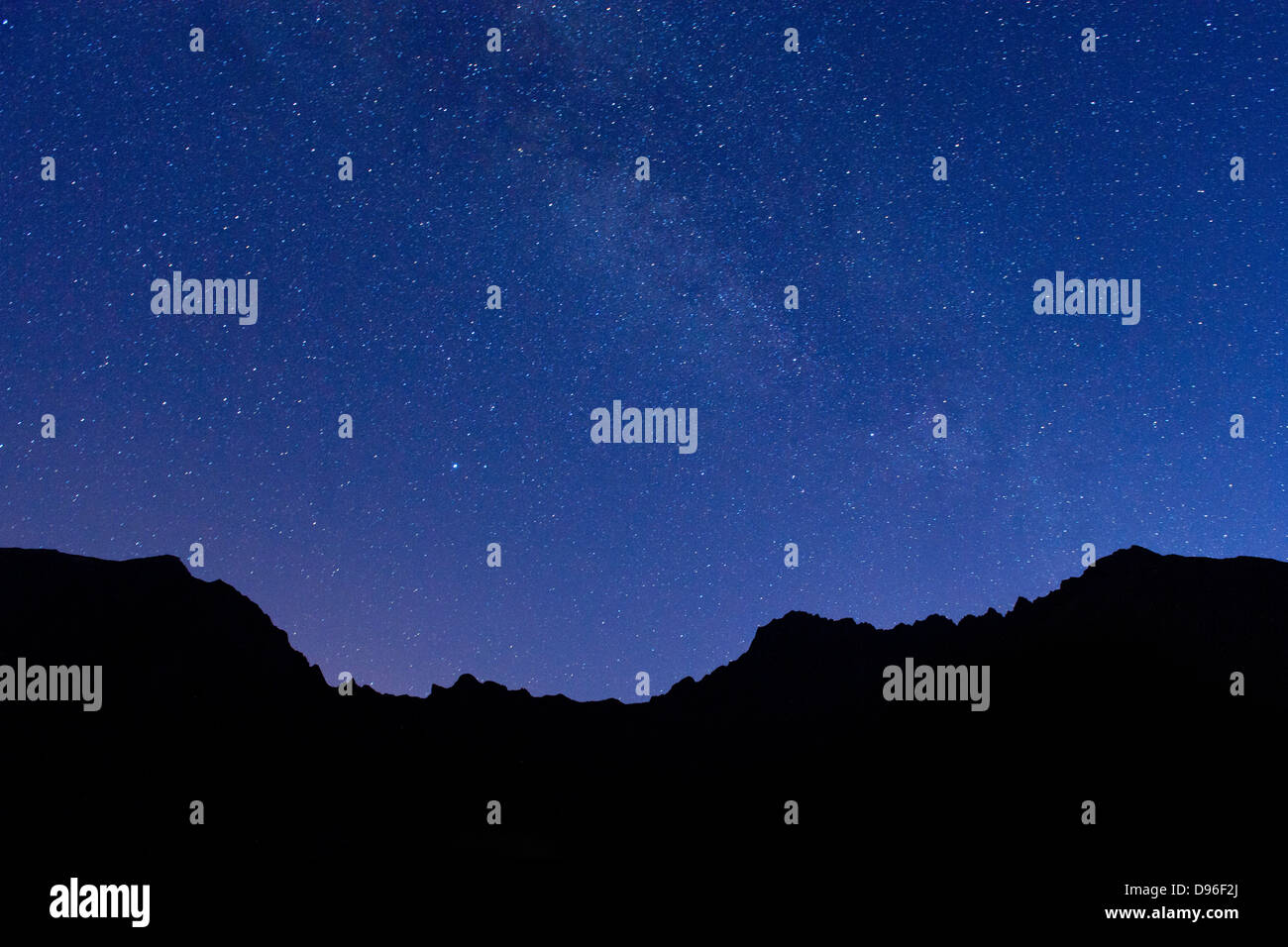 Stars and the outline of the mountain peaks encircling the Cirque de Cilaos caldera on the French island of Reunion. - Stock Image