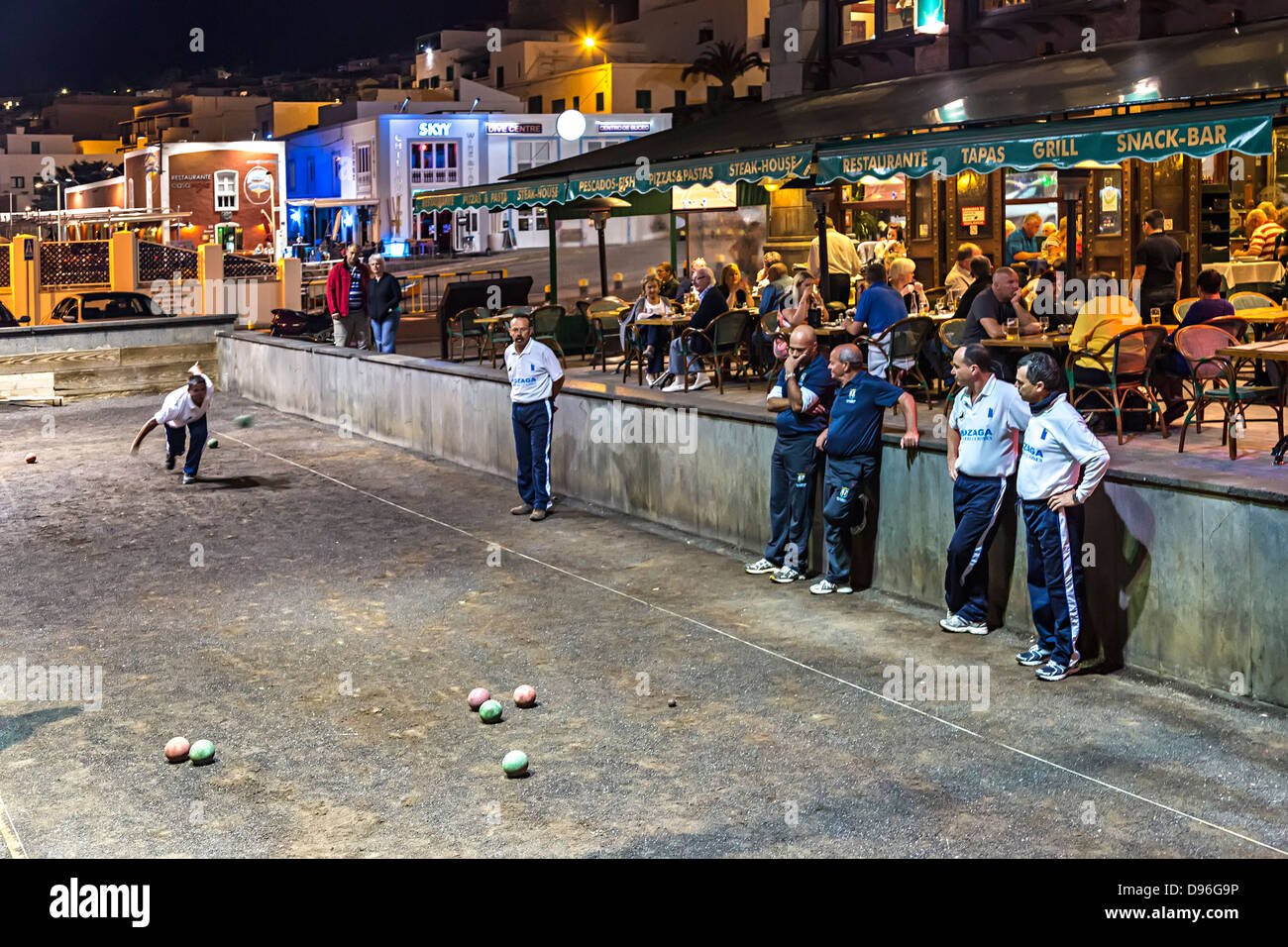 Locals playing patanque at night in front of tourist restaurants, Puerto del Carmen, Lanzarote, Canary Islands, - Stock Image