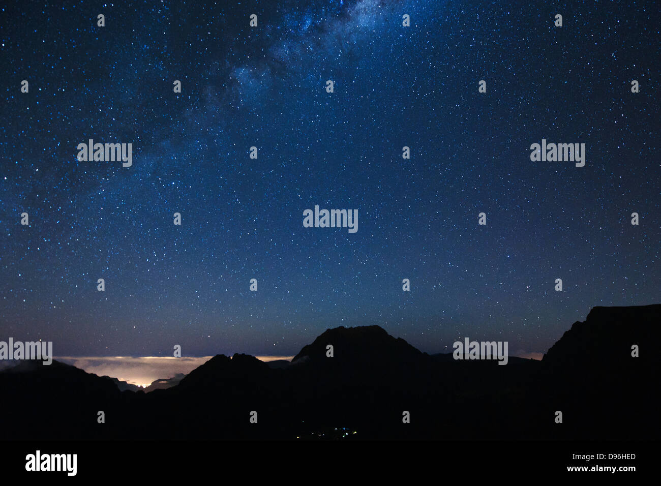 The Milky Way and the silhouette of the mountains encircling the Cirque de Mafate caldera on the French island of - Stock Image
