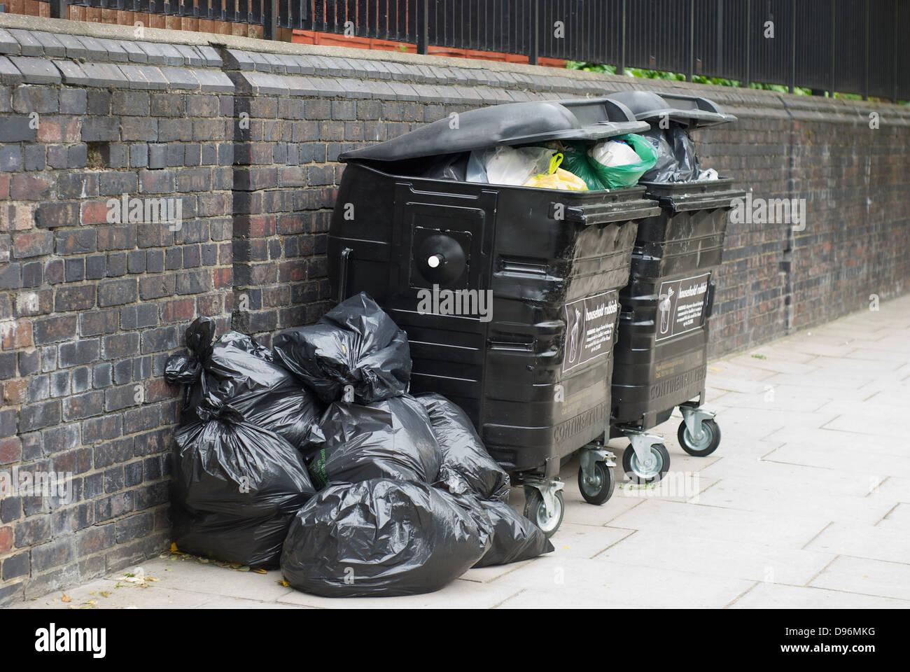Overloaded rubbish bins in St. John's Wood London UK Stock Photo