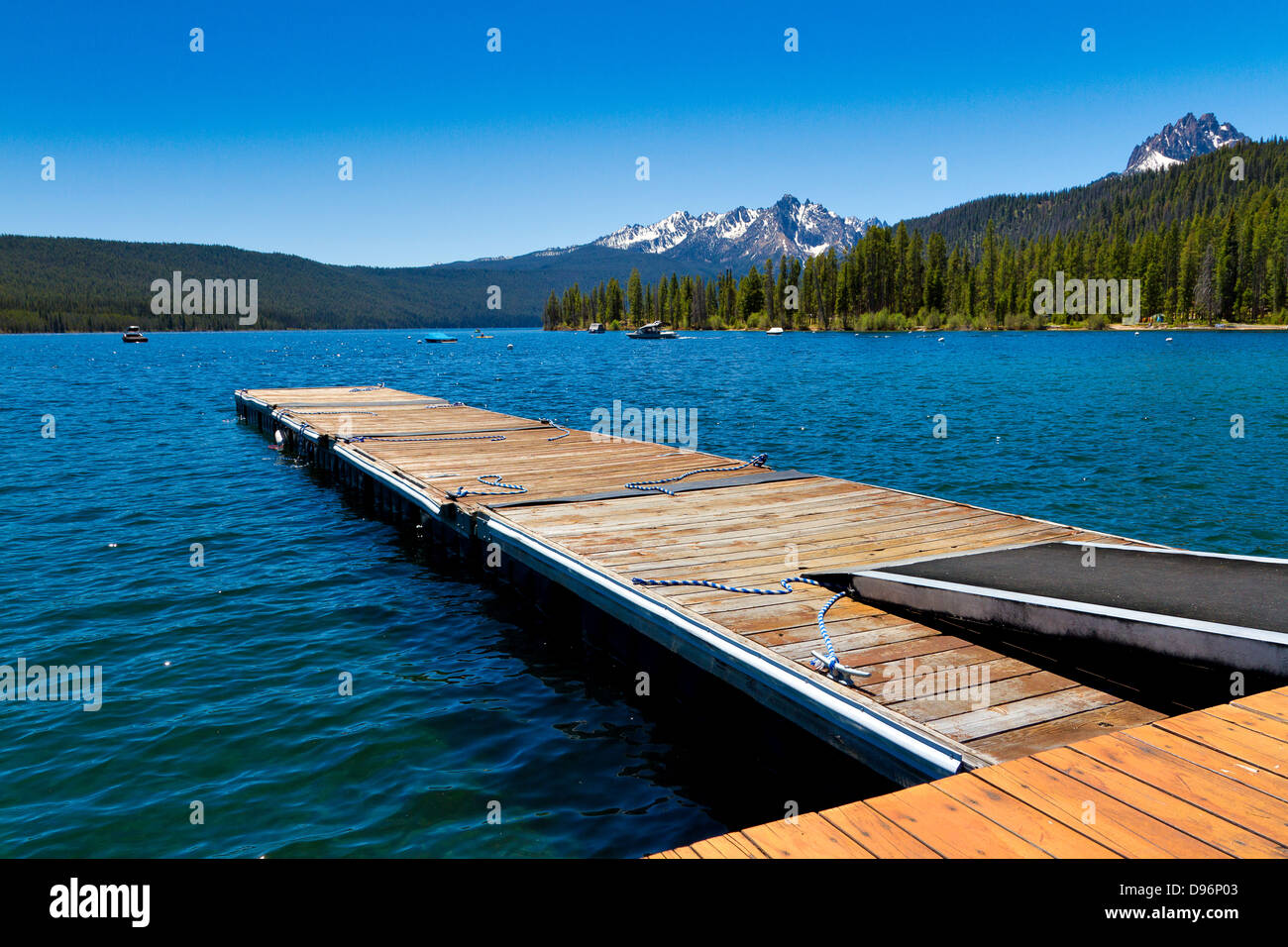 Wooden boat dock at north end of Redfish Lake with snowcapped mountains in background on clear summer day in Stanley, Stock Photo