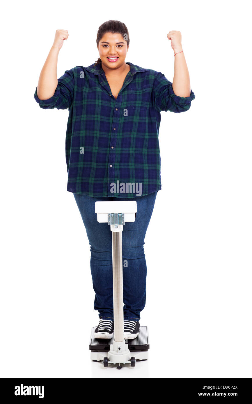 happy overweight woman waving fists when noticed she lost some weight - Stock Image