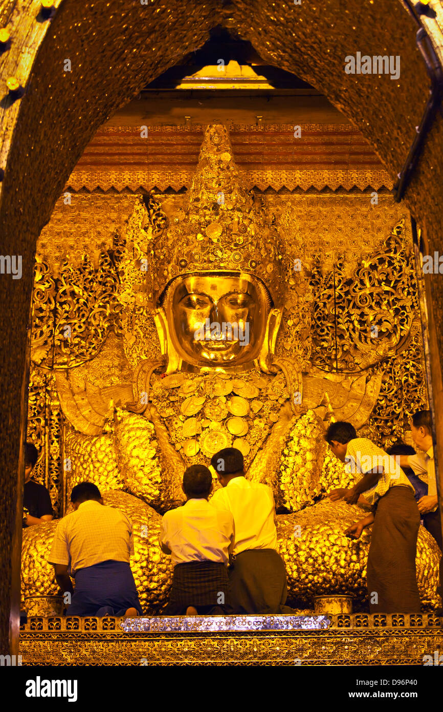 BURMESE MEN gild the much venerated MAHAMUNI BUDDHI inside the MAHAMUNI PAYA built by King Bodwpaya in 1784 - MANDALAY, Stock Photo