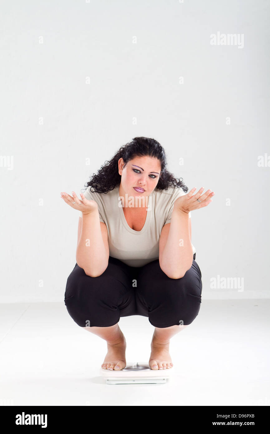 overweight woman on scale feeling hopeless - Stock Image
