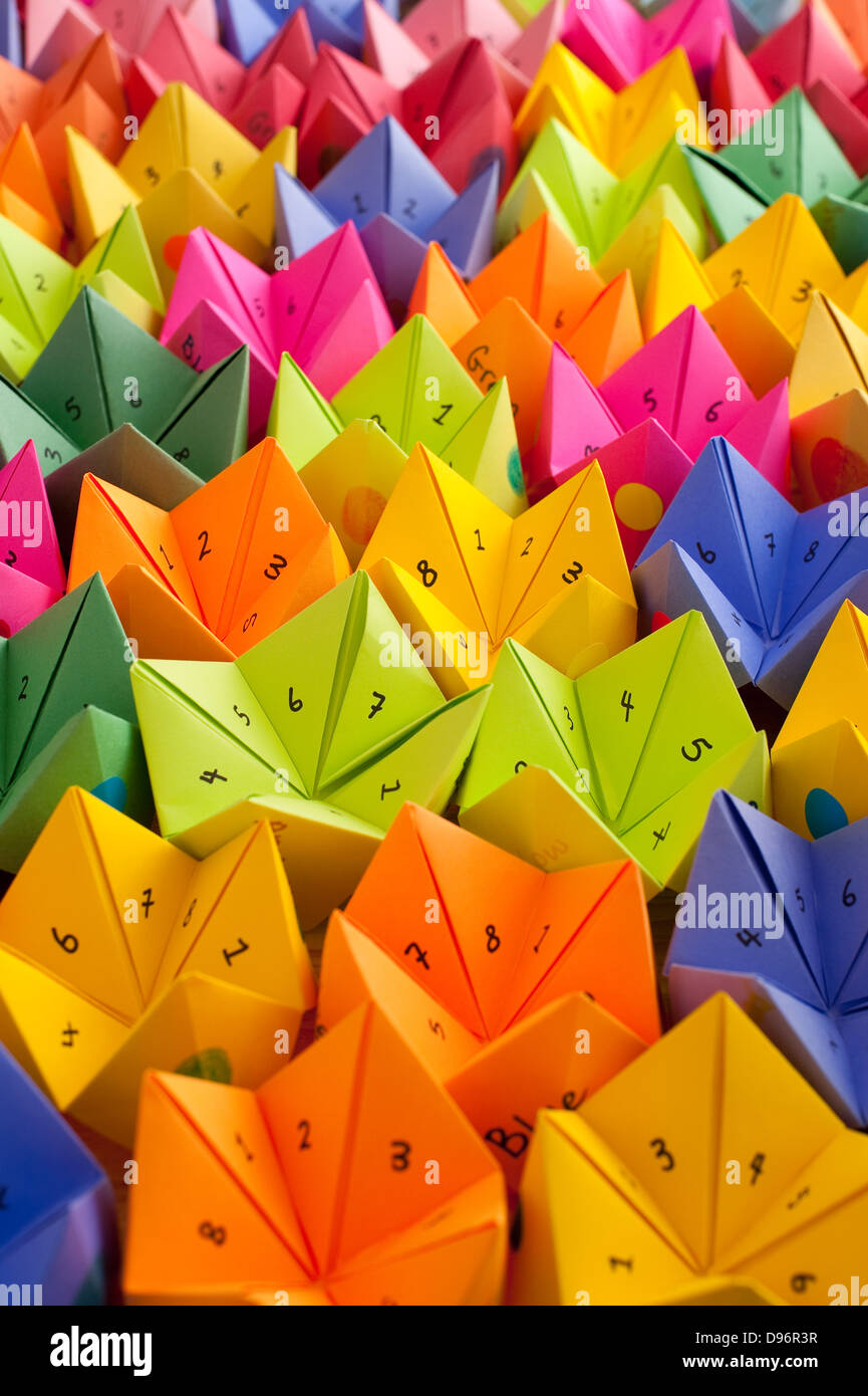Multicolored cootie catchers, origami fortune teller with numbers and positive words of encouragement game of chance - Stock Image