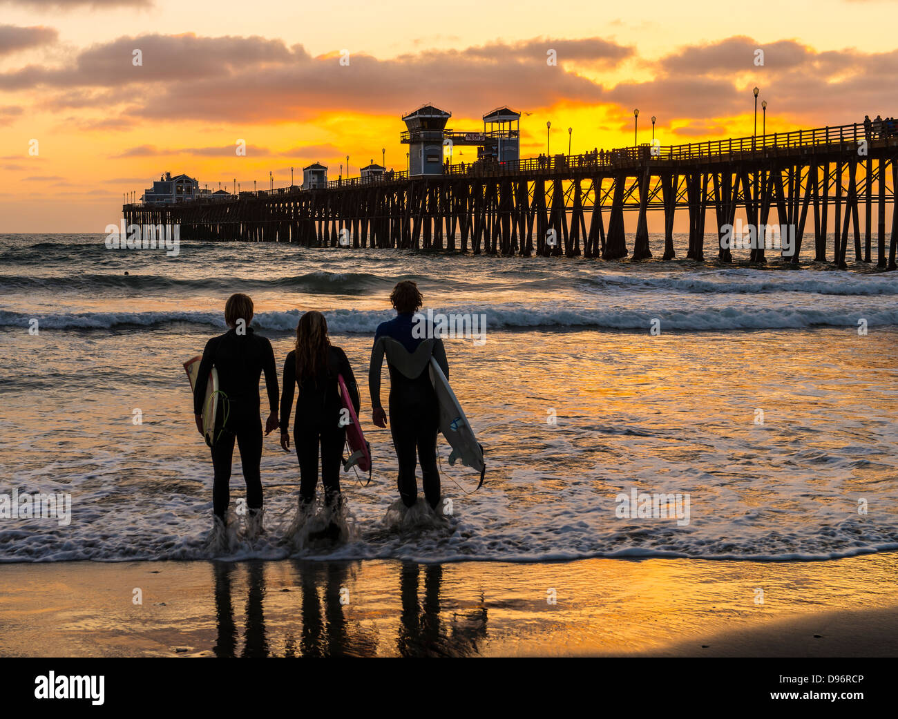 surfer friends watching a sunset in oceanside california stock