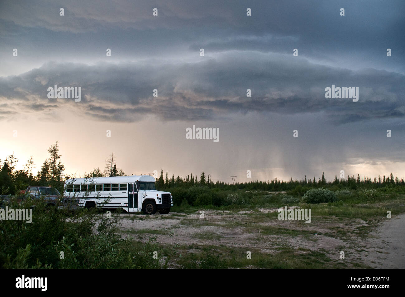 Dark clouds of a summer storm pour rain over the tundra near the town of Churchill, Manitoba, Canada. - Stock Image