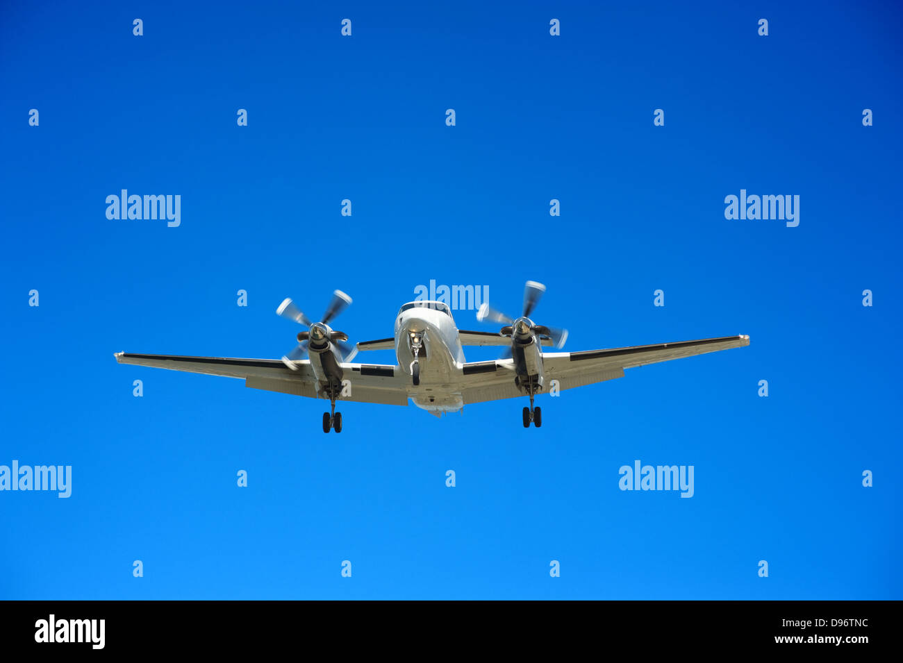 Twin engine propeller airplane approaching for landing - Stock Image