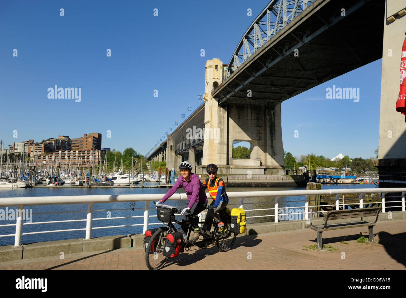 Bicyclists ride along the False Creek seawall walkway with the Burrard street bridge above, Vancouver British Columbia. - Stock Image