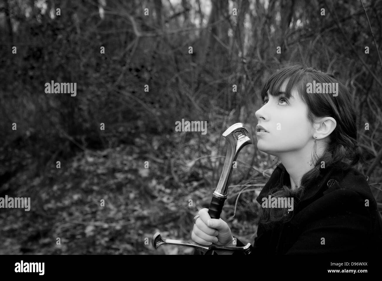 Beautiful young woman holds sword hilt and gazes imploringly at sky - Stock Image