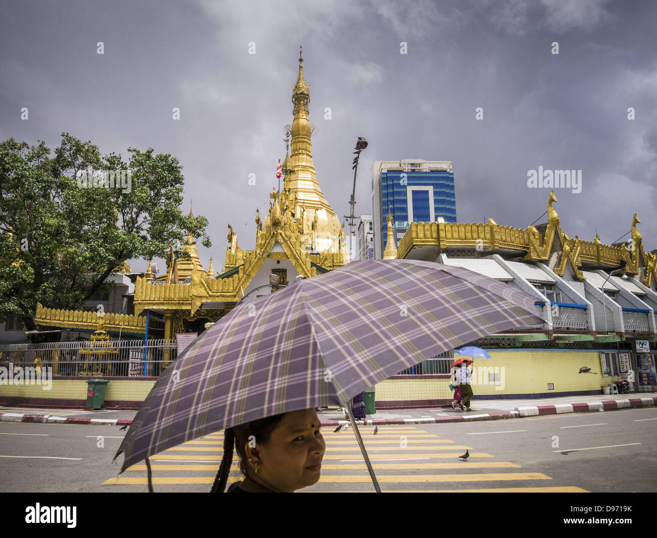June 12, 2013 - Yangon, Union of Myanmar - A woman walks past Sule Pagoda in Yangon, Myanmar. Sule Pagoda is one - Stock Image