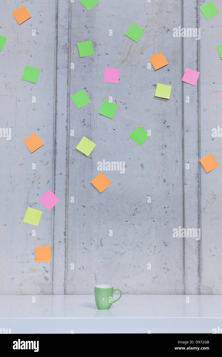 Germany, North Rhine Westphalia, Cologne, Adhesive notes stuck on wall with coffee cup in foreground Stock Photo