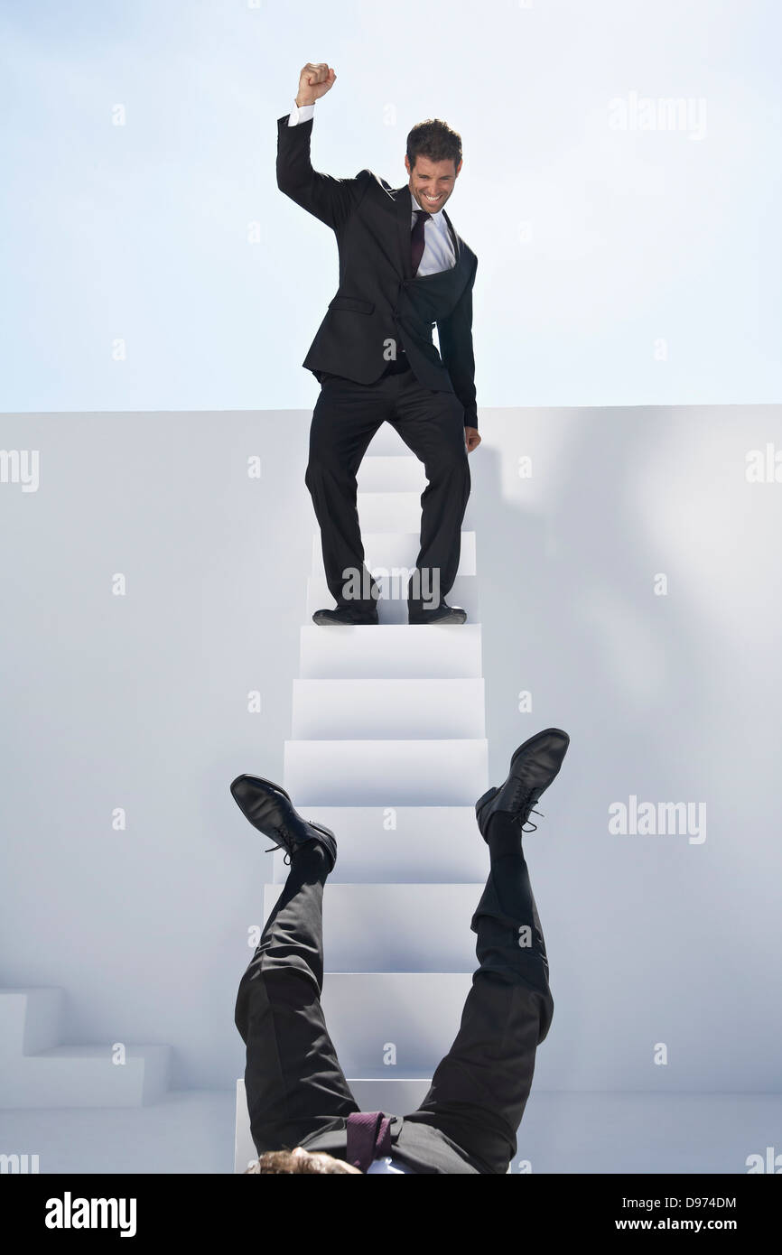Businessman standing on stairs and other one falling down - Stock Image