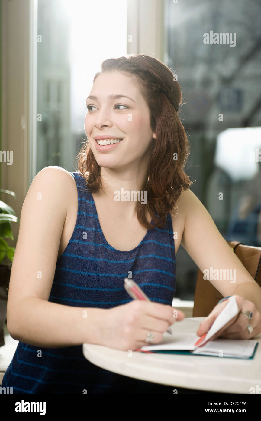 Germany, Bavaria, Munich, Young woman writting in diary, smiling - Stock Image