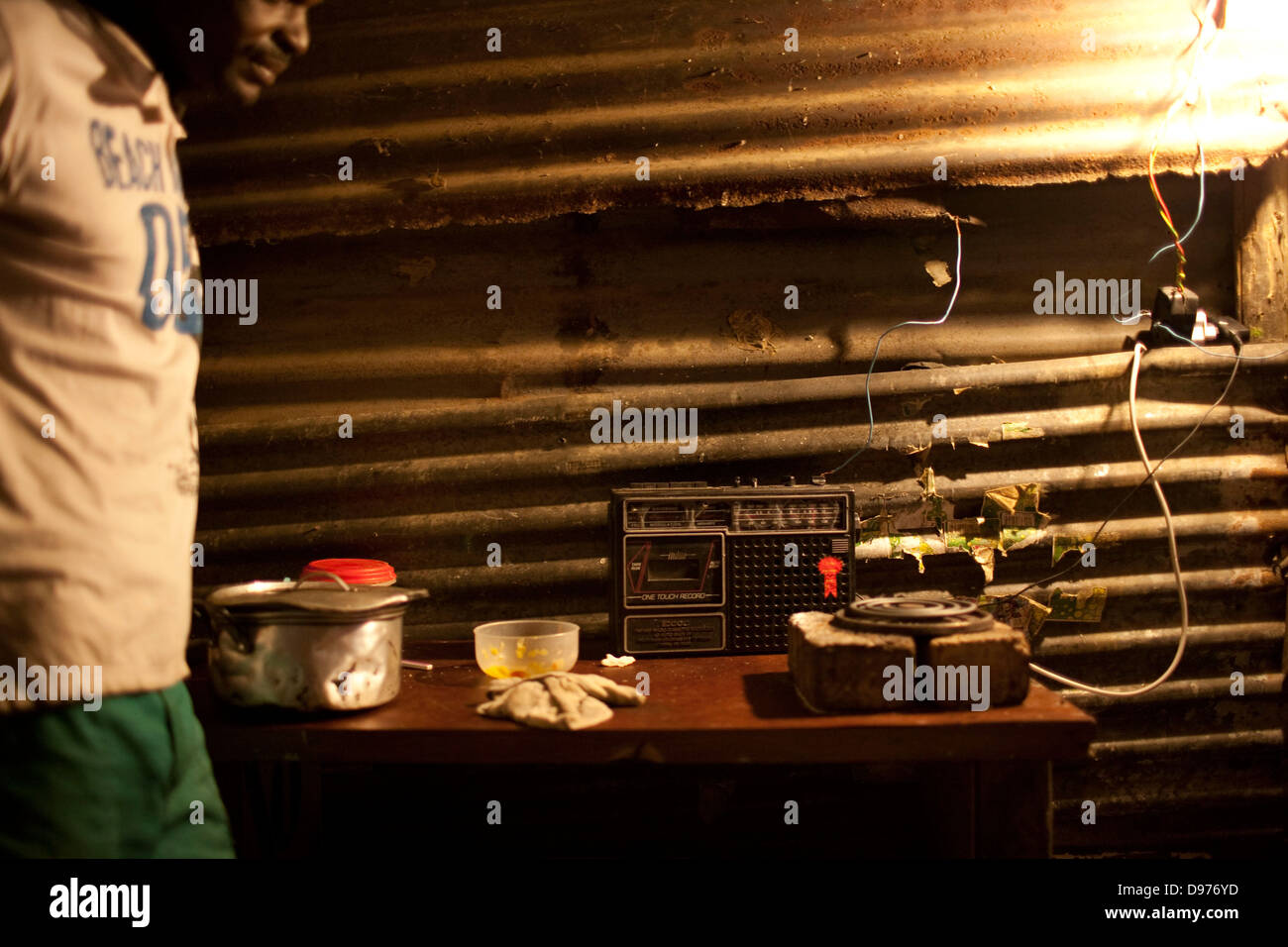 <p>Lazros Mafinya 36 listens to radio home in ice-cream factory He has been living here family 10 years He - Stock Image