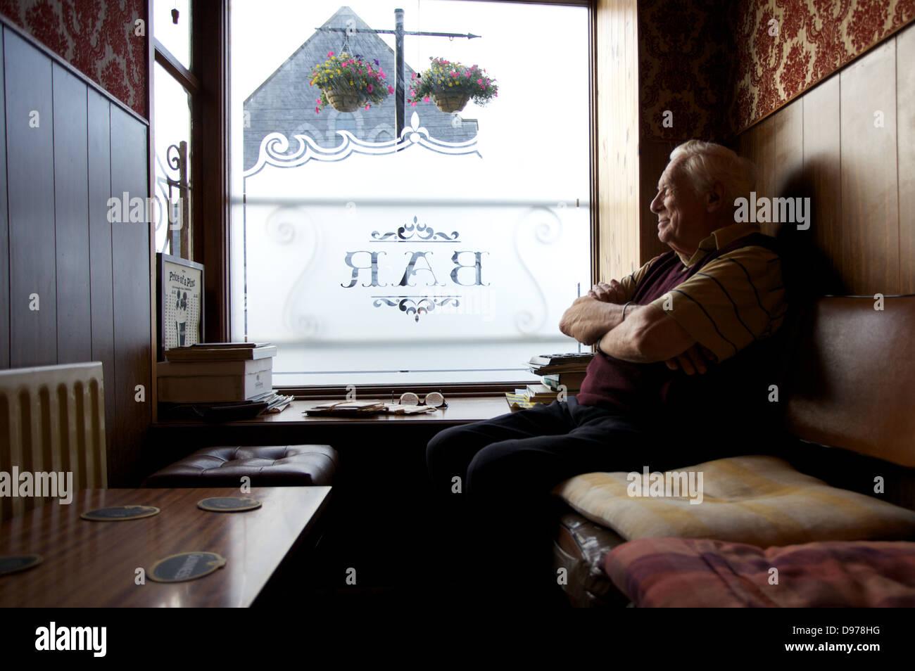 An elderly gentleman sitting in a bar in County Galway in Ireland. - Stock Image
