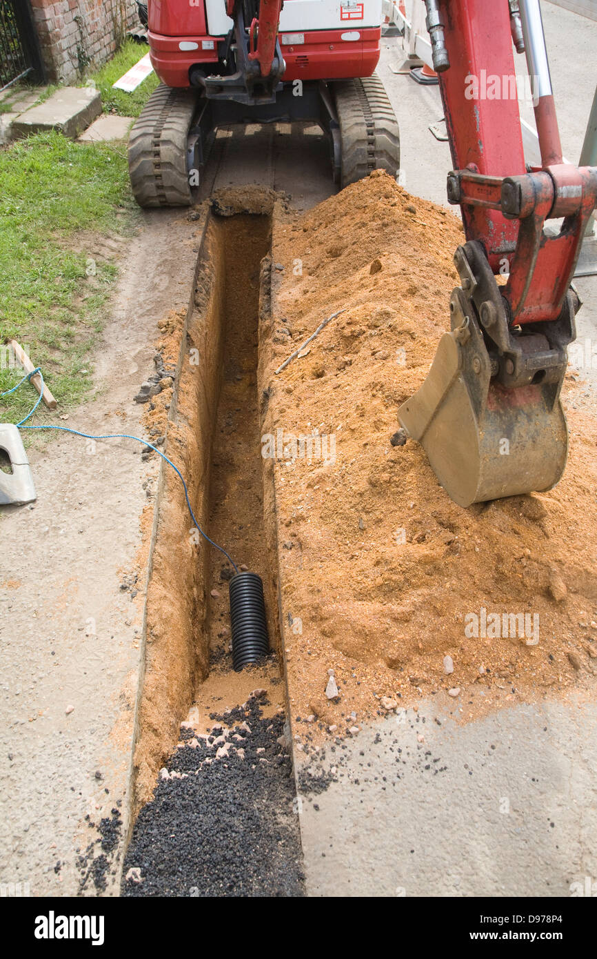 Digging a trench to take electricity supply cables underground, Shottisham, Suffolk, England - Stock Image