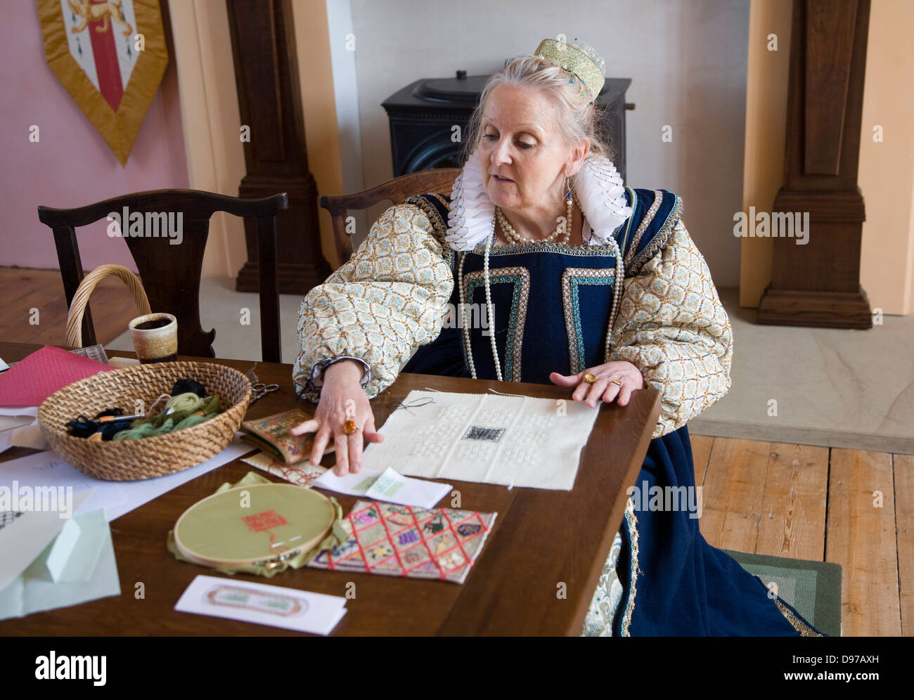 Seamstress in Tudor costume explaining sewing methods during history re-enactment day at Layer Marney Tower, Essex, - Stock Image