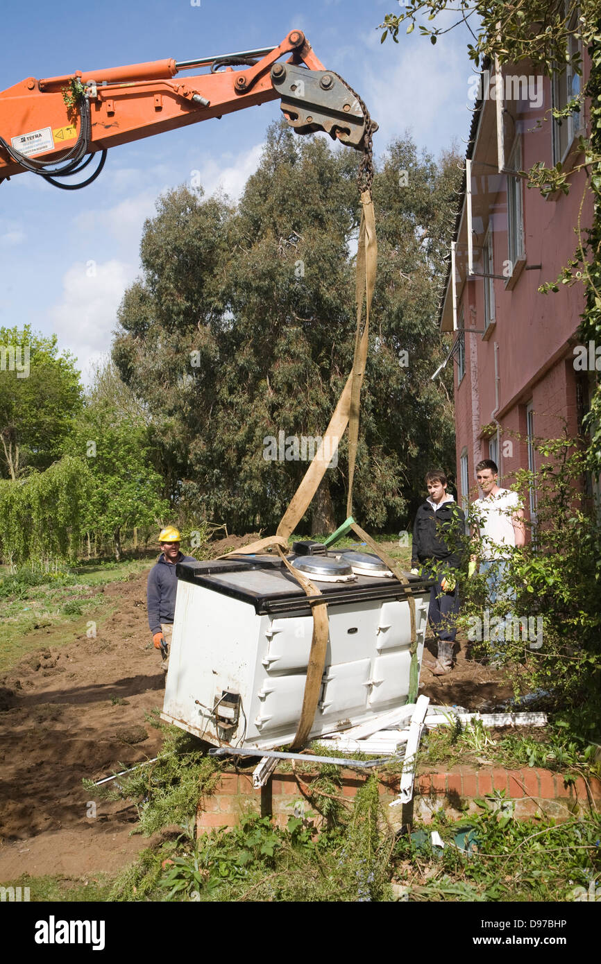 Crane and workmen removing Aga cooker from house about to be demolished, Shottisham, Suffolk, England - Stock Image