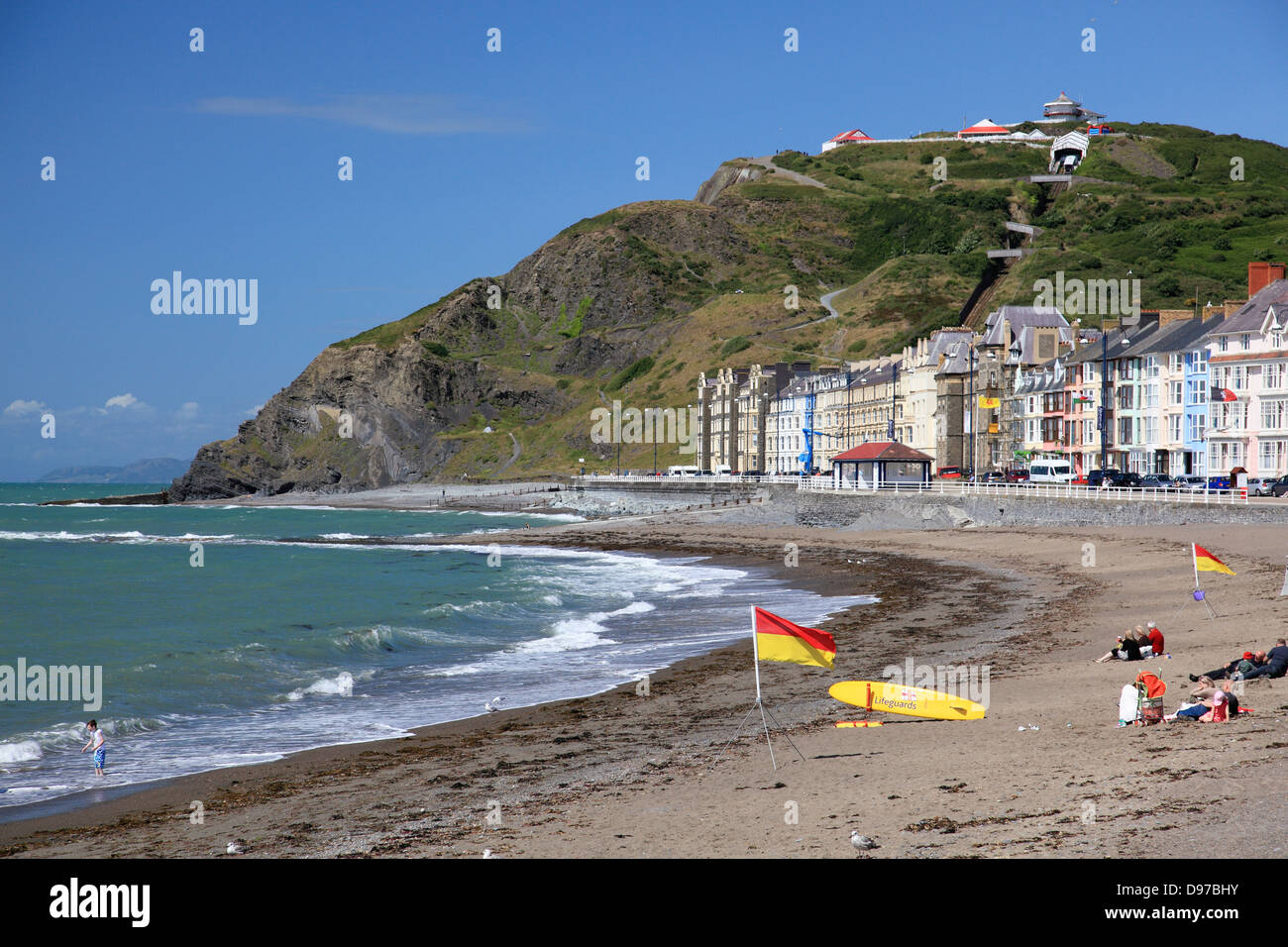 The Beach and promenade at Aberystwyth with RNLI flags to show a safe swimming area and a lifeguard on duty - Stock Image