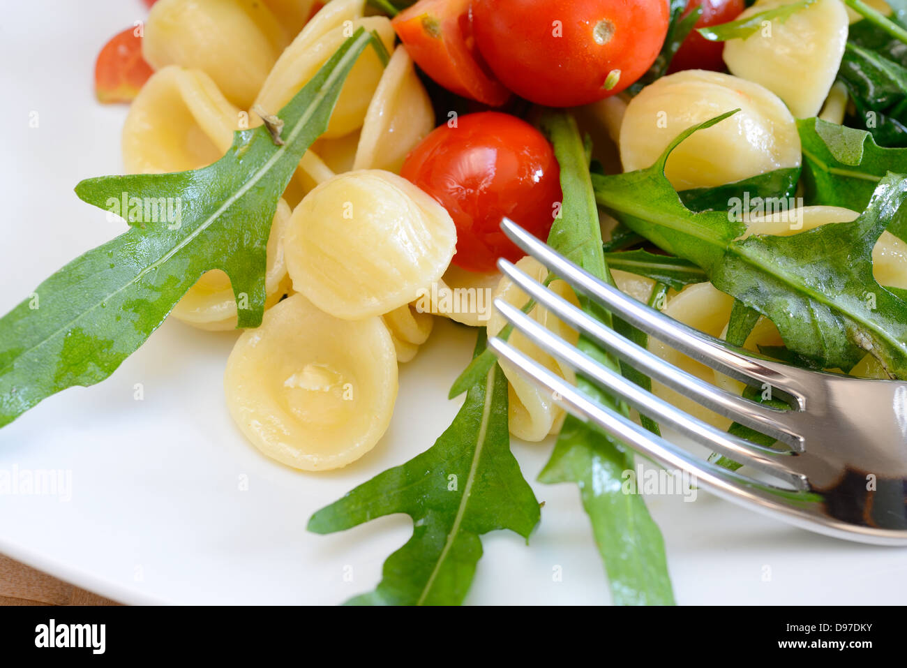 orecchiette pasta with rocket and little tomatoes to be served cold Stock Photo