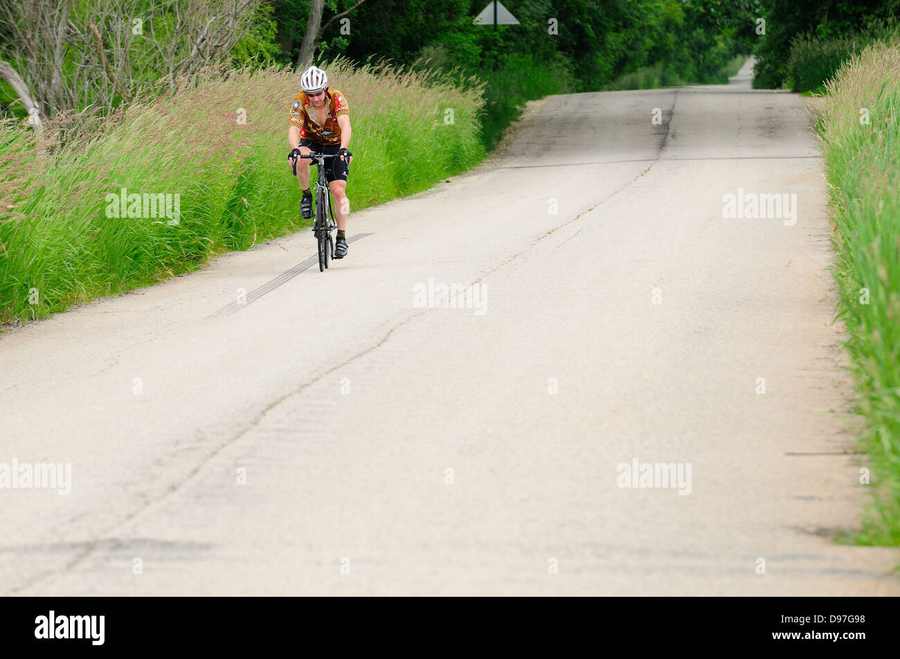 Lone bicyclist on country road. - Stock Image