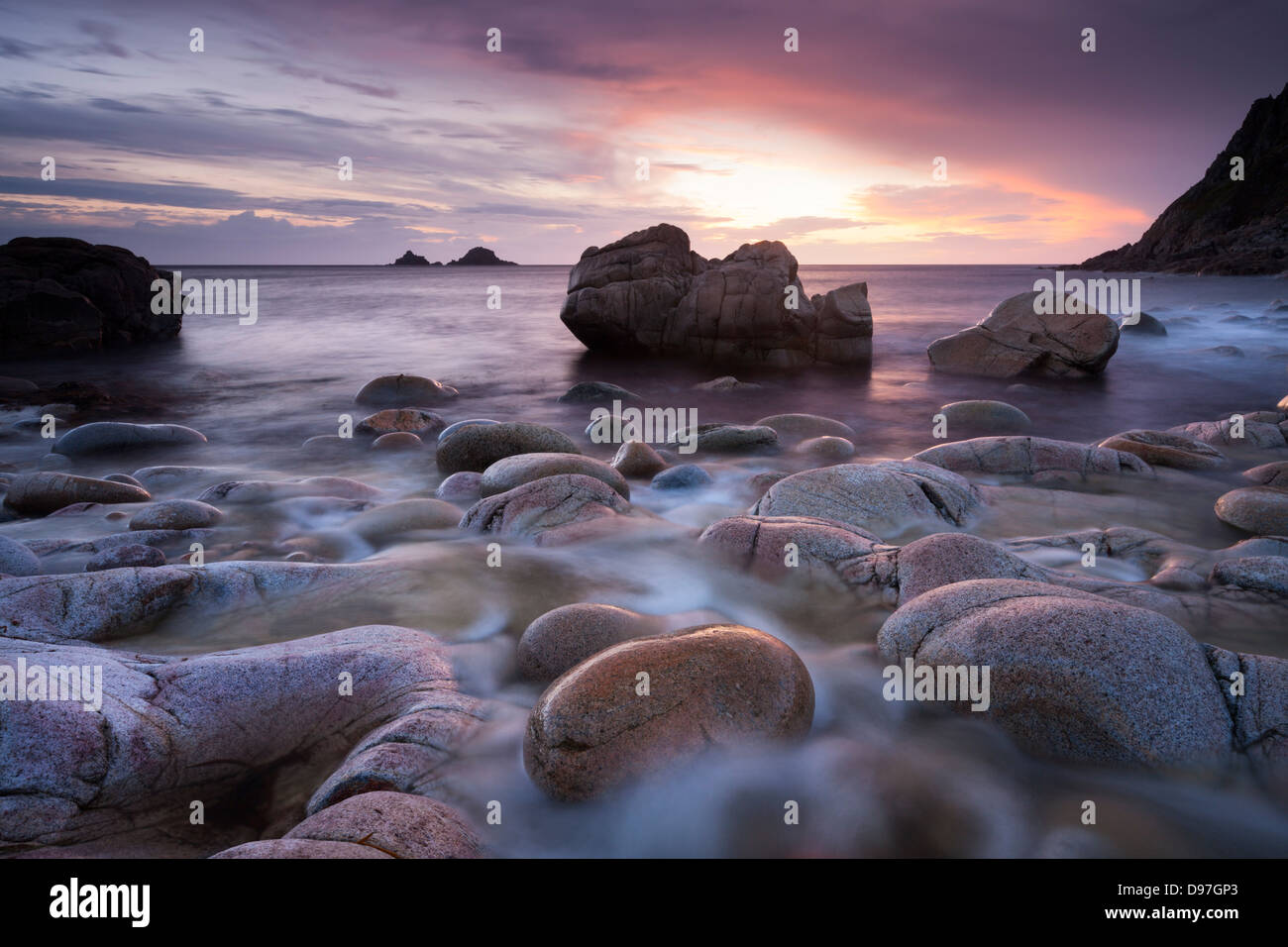 Sunset over the Brisons and Porth Nanven, a rocky cove near Land's End, Cornwall, England. Spring (April) 2012. - Stock Image