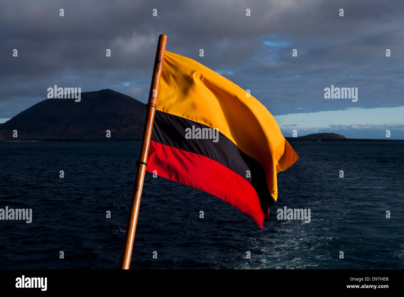 The Ecuadorian flag fills the foreground when looking back from the Grand Odyssey yacht towards James Island, the - Stock Image