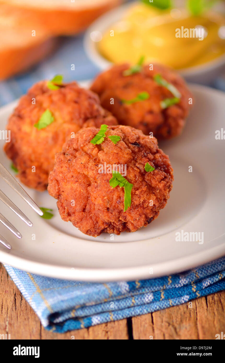 meat balls with mustard on white dish on wooden backgrounds - Stock Image