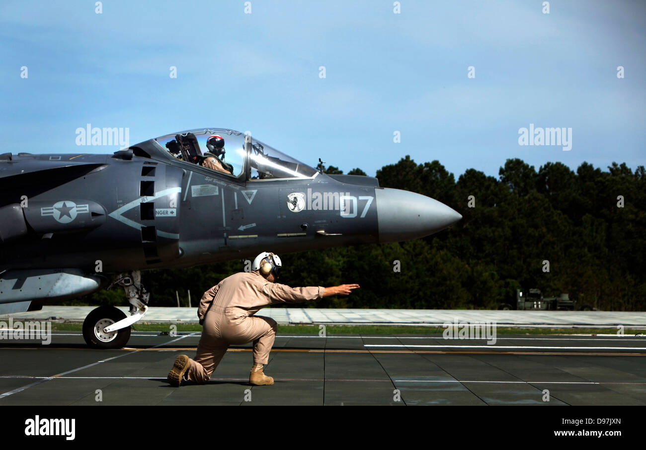 A US Marine Corps AV-8B Harrier jump jet aircraft is given the signal to take off during aircraft carrier qualifications - Stock Image