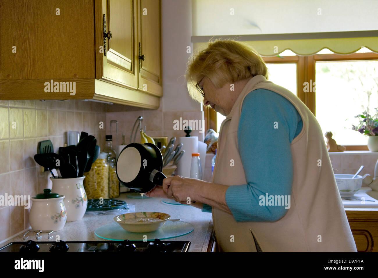 Senior lady pouring porridge into bowl in kitchen - Stock Image