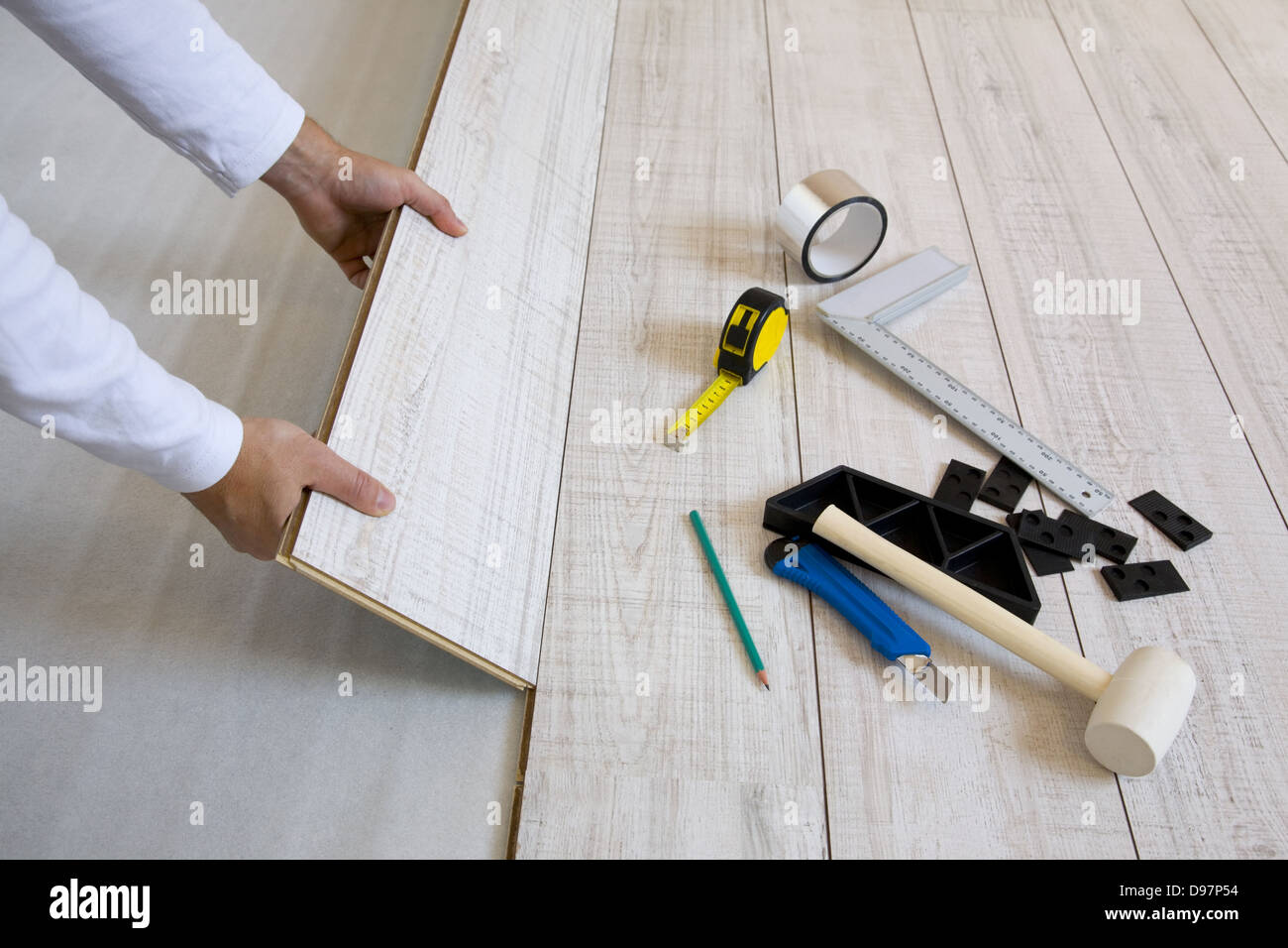 Worker laying a floor with laminated flooring boards - Stock Image