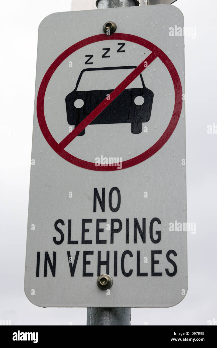 No sleeping in vehicles - road sign seen in Victoria, Australia during rainy day. - Stock Image