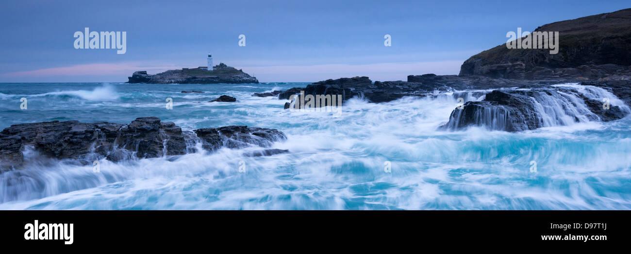 Waves crash around the rocks near Godrevy Lighthouse, Cornwall, England. Winter (February) 2013 - Stock Image