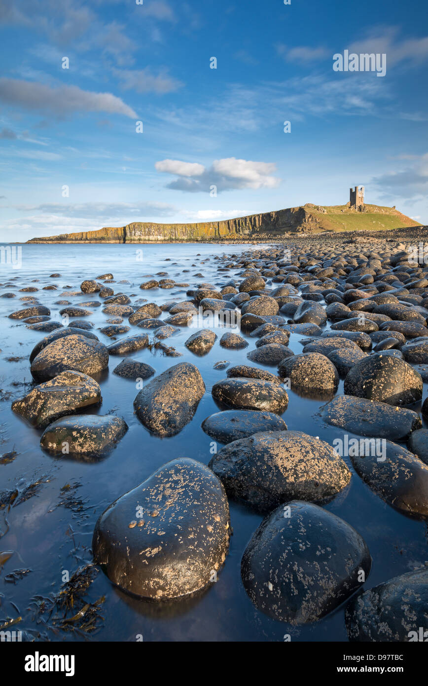 Afternoon sunshine on Dunstanburgh Castle, viewed from the boulder strewn shores of Embleton Bay, Northumberland, - Stock Image