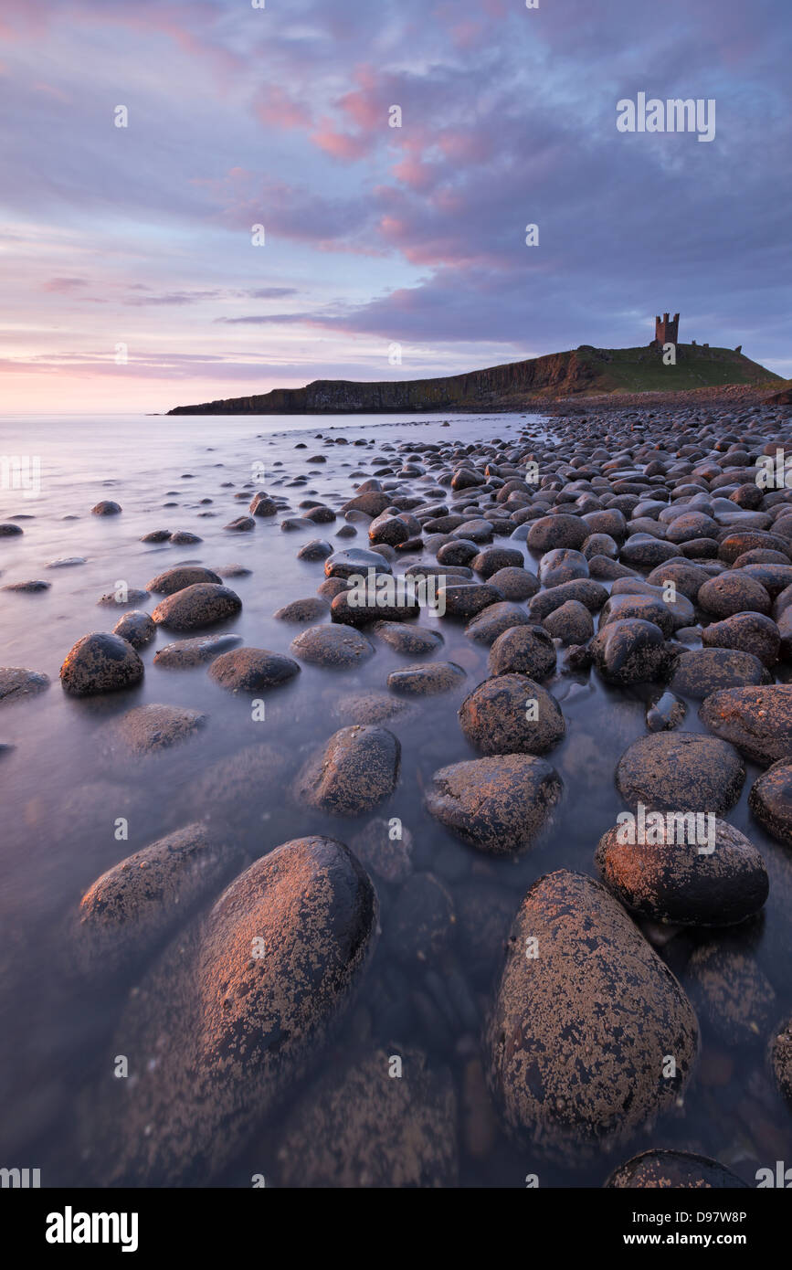 Dunstanburgh Castle from Embleton Bay at dawn, Northumberland, England. Spring (May) 2013. - Stock Image