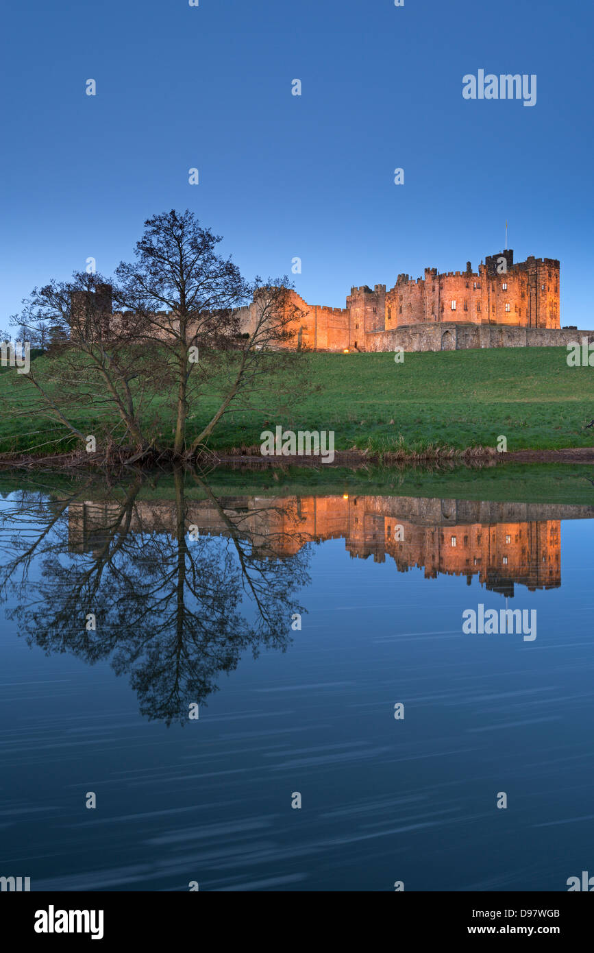 Alnwick Castle reflected in the River Aln at twilight, Northumberland, England. Spring (May) 2013. - Stock Image