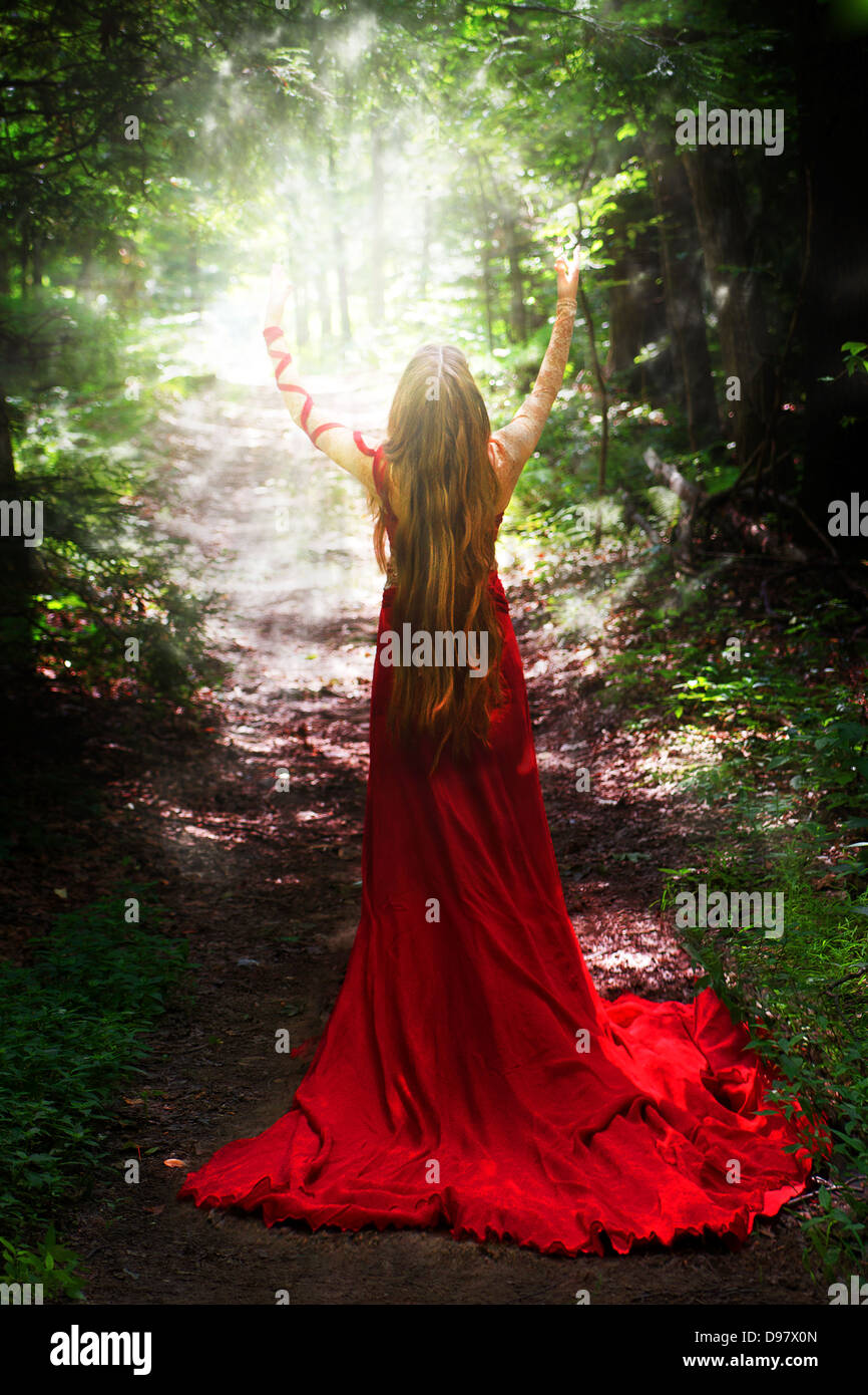 Back view of young woman with long hair & red medieval dress with long train extending arms to conjure burst - Stock Image