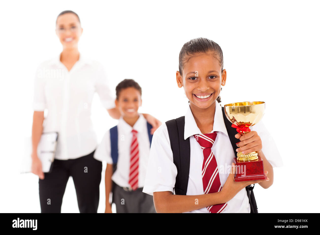 schoolgirl holding trophy in front of teacher and classmate - Stock Image
