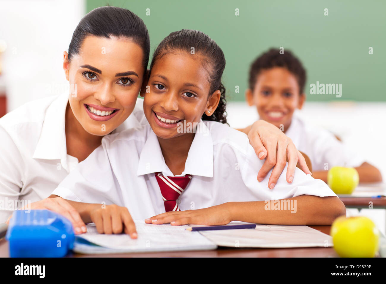 pretty elementary school educator and students in classroom - Stock Image