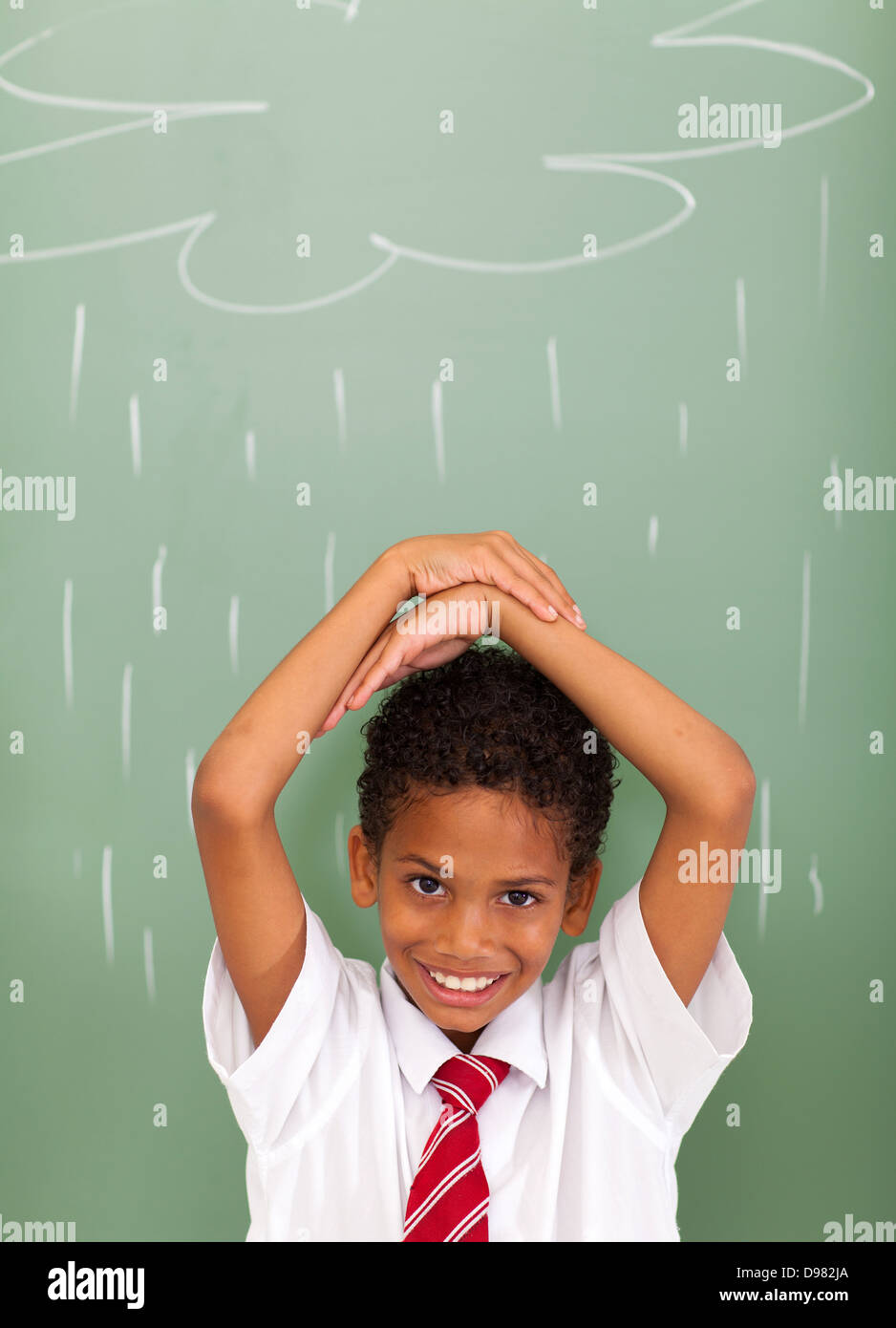 elementary school student in front of rain cloud drawn on chalkboard - Stock Image
