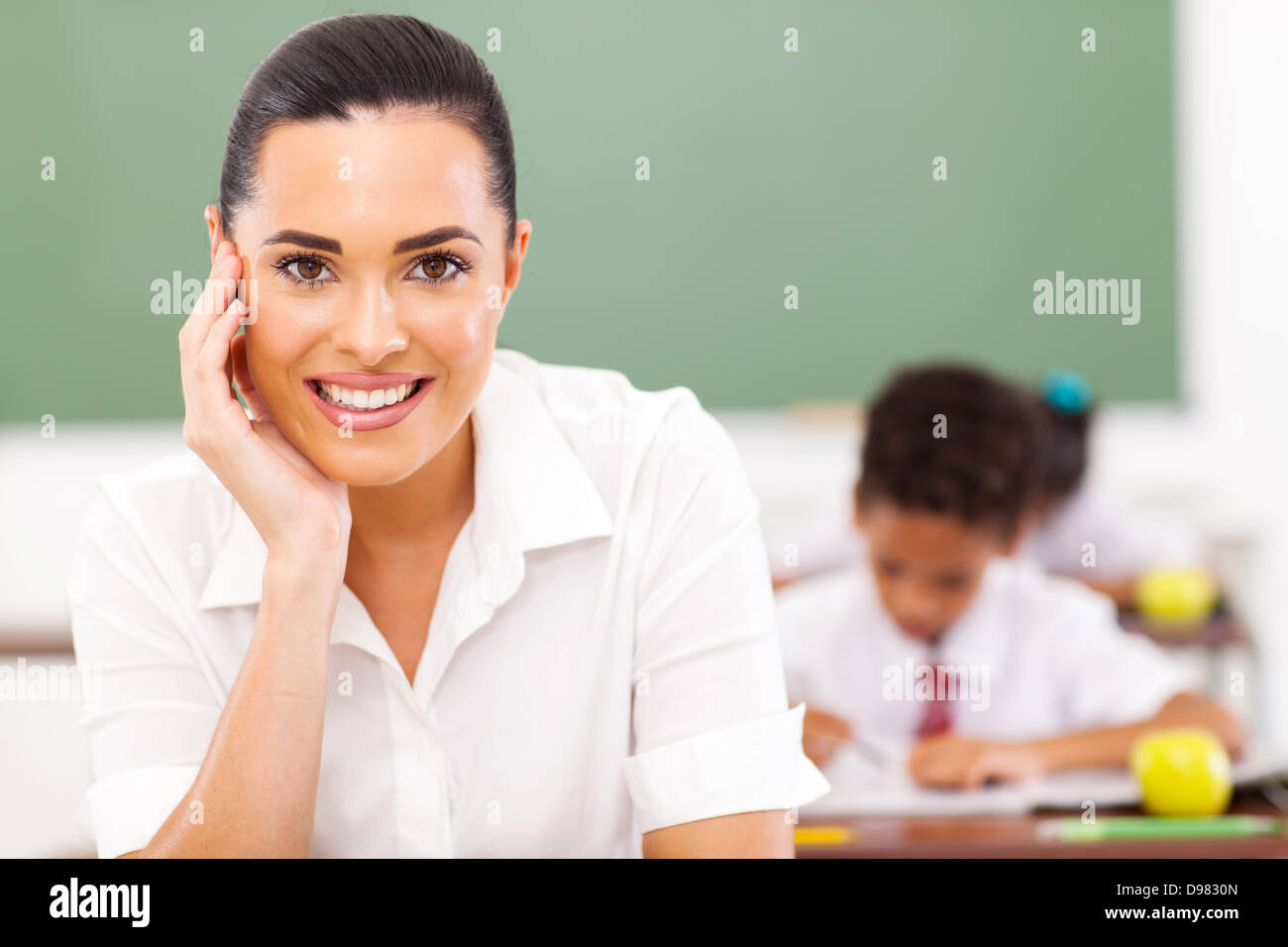 elementary school educator siting in classroom - Stock Image