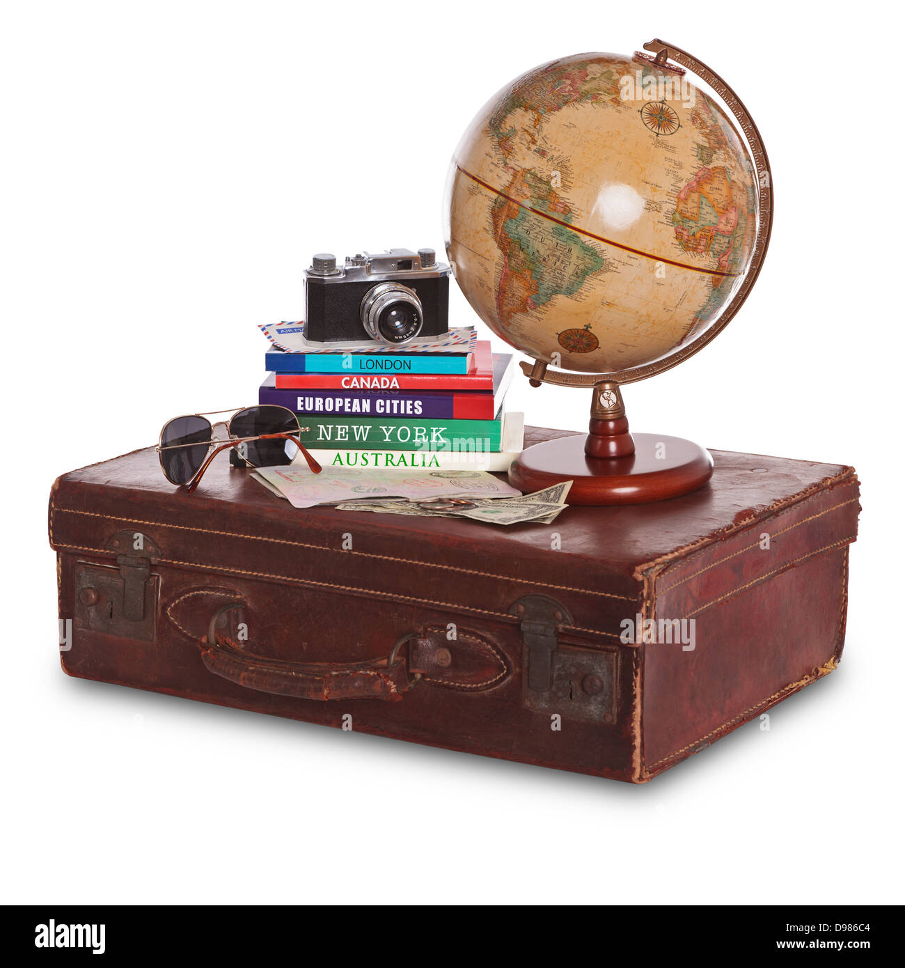 Still-life photo of an old brown leather suitcase with camera, travel guides, world globe, sunglasses, stamped passport Stock Photo