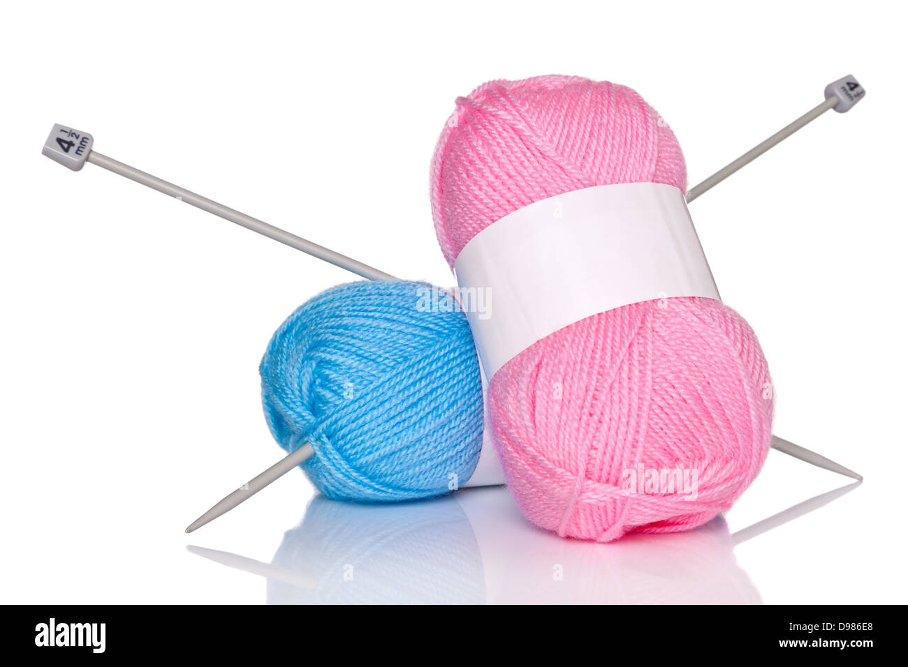 Balls of wool and knitting needles isolated on a white background. - Stock Image