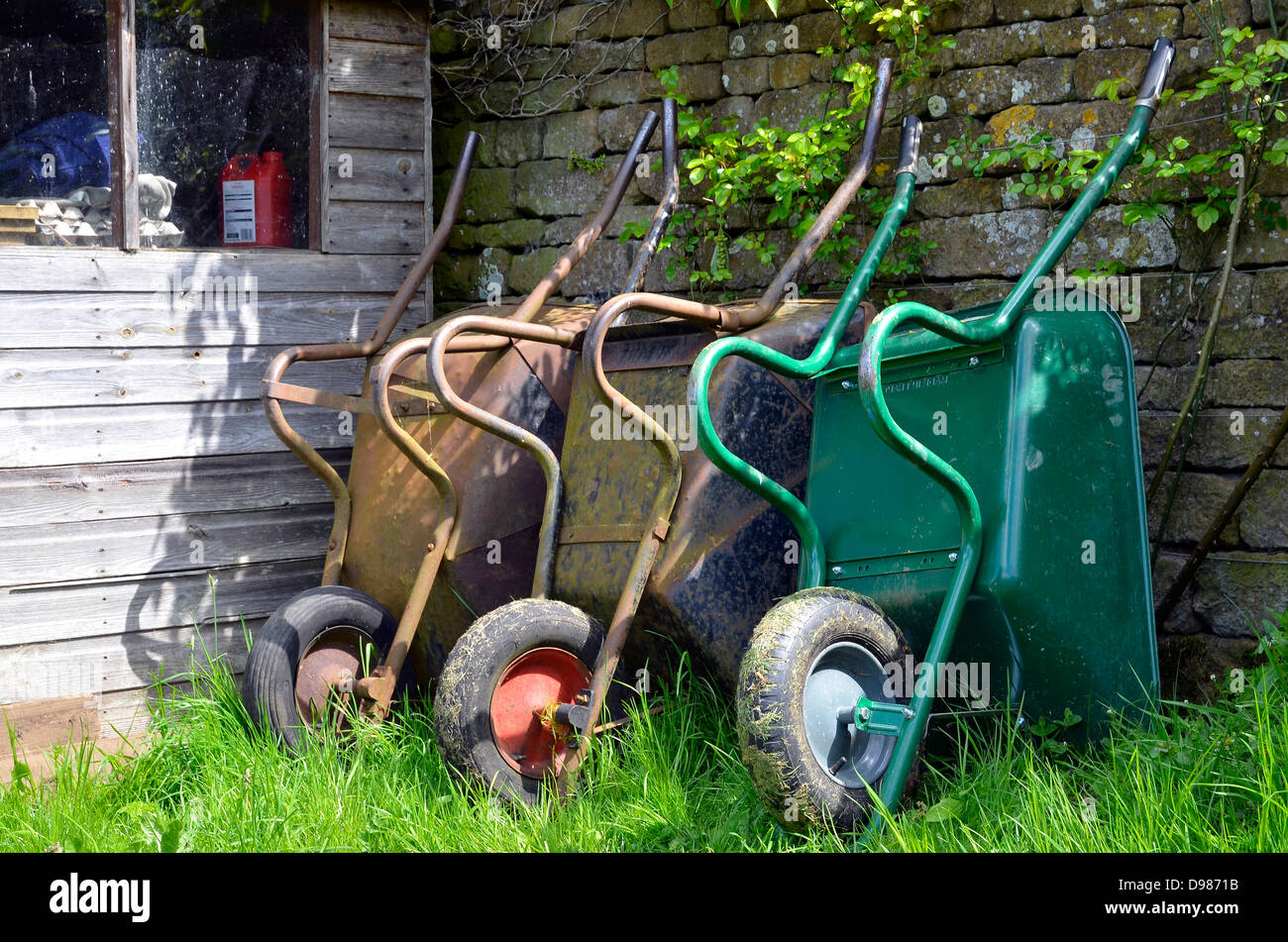 Wheelbarrows leaning against a wall by a garden shed. - Stock Image