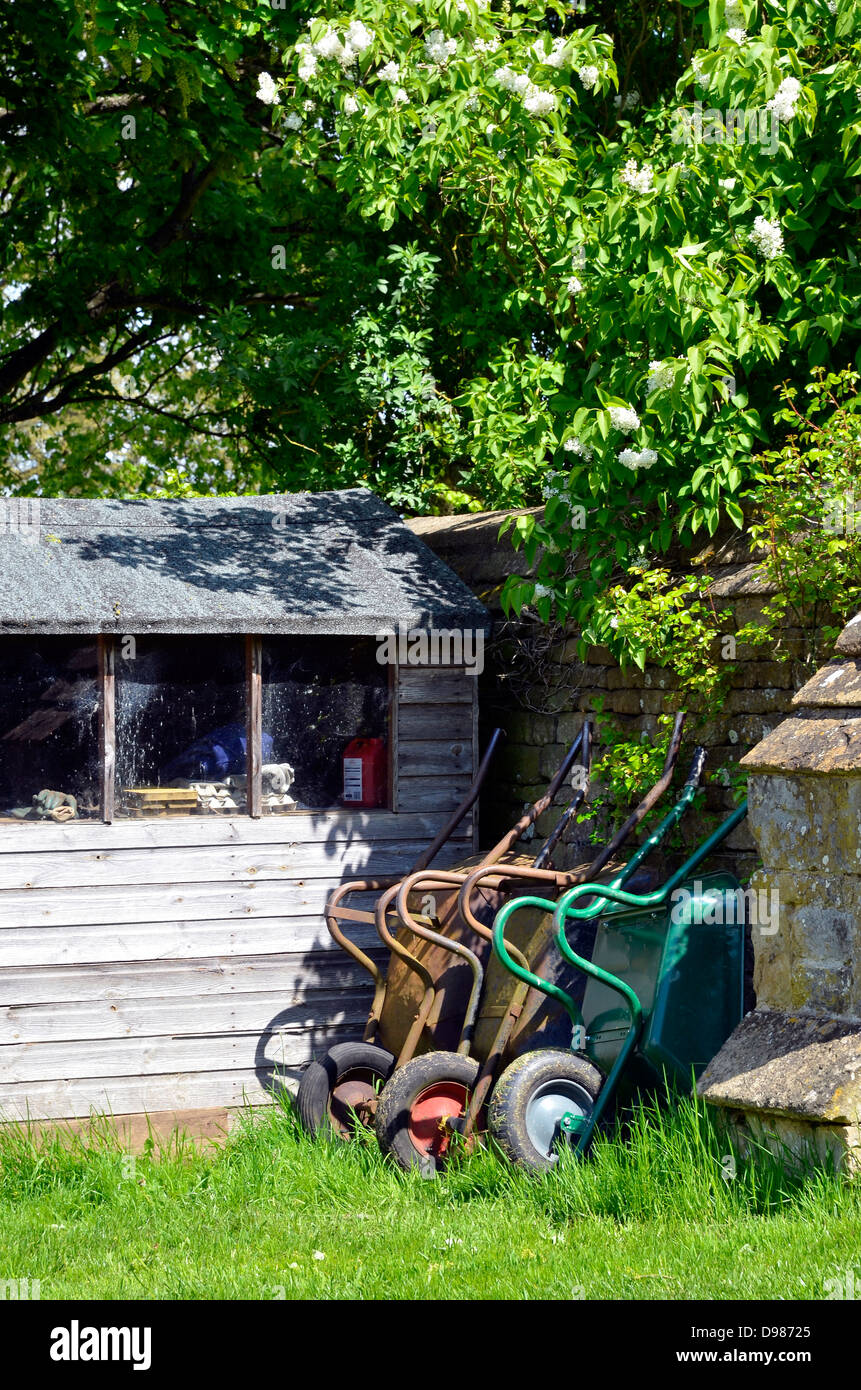 1ab520e1785 Wheelbarrows leaning against a wall by a garden shed. - Stock Image