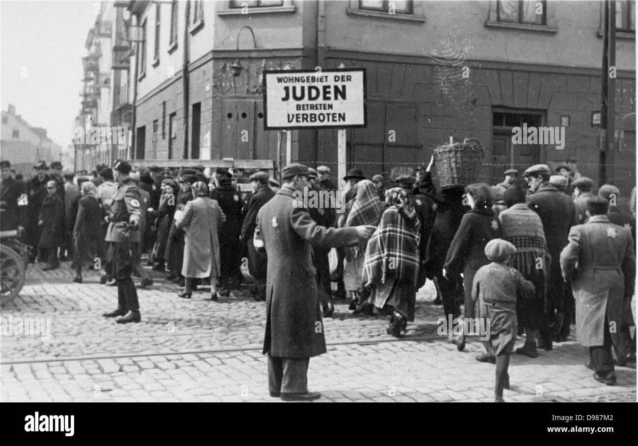 A Jewish policeman and a German soldier direct pedestrian traffic across the main street dividing the two parts - Stock Image