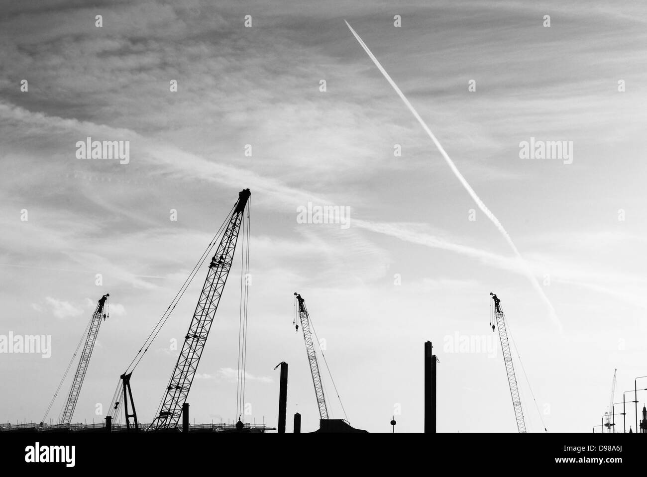 Heavy construction cranes seen silhouetted on the skyline of London, - Stock Image